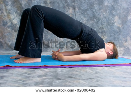 an athletic brown haired woman is doing yoga exercise  Setu Bandhasanasana or bridge pose on in studio against mottled background.