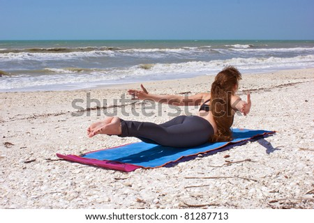 an athletic brown haired woman is doing yoga exercise Shalabhasana or locust  pose on an empty beach at the gulf of mexico in bonita springs florida - stock photo