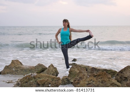 an athletic brown haired woman is doing yoga exercise standing hand to toe pose in the ocean water at the gulf of mexico in naples florida at sunset - stock photo