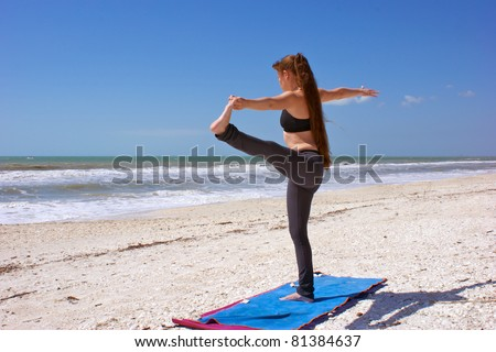 an athletic brown haired woman is doing yoga exercise standing hand to toe pose on an empty beach at the gulf of mexico in bonita springs florida