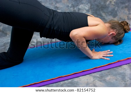 An athletic brown haired woman is doing yoga exercise Sunbird posture on yoga mat in studio with mottled background. - stock photo