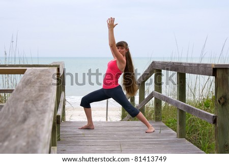an athletic brown haired woman is doing yoga exercise warrior 1 pose on boardwalk at beach in the gulf of mexico in naples florida at sunset. - stock photo