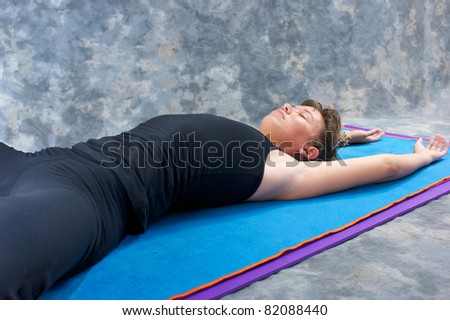 an athletic brown haired woman is stretched out on yoga mat with hands above head in studio with a mottled grey background. - stock photo