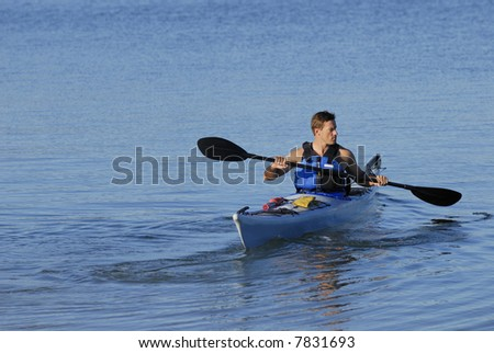 An athletic man is backing off the shore into calm blue waters of Mission Bay, San Diego, California. Copy space on top and left. - stock photo