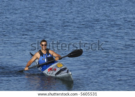 An athletic man is showing off his kayaking skills in calm waters of Mission Bay, San Diego, California.
