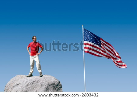 An athletic patriotic youth on top of a boulder