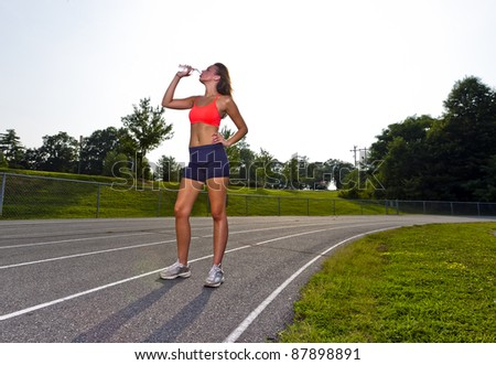 An athletic teenager exercising on a track outdoors - stock photo