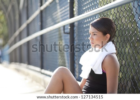An athletic teenager sitting,resting,and thinking with a serious, worried look. - stock photo