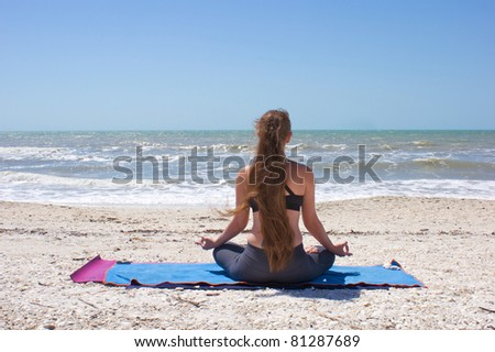 an athletic woman is doing yoga exercise half lotus or Ardha Padmasana with hands in om mudra position on an empty beach at the gulf of mexico in bonita springs florida with long hair blowing in wind - stock photo