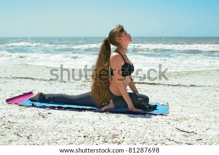 an athletic woman is doing yoga exercise on beach in Kapotasana or Pigeon Pose with leg stretched back on an empty beach at the gulf of mexico in bonita springs florida with long hair blowing in wind - stock photo