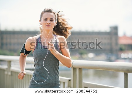 An athletic woman is jogging on a bridge, listening to music. Her long hair is up in a ponytail and blowing in the wind. - stock photo