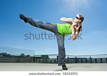 An athletic woman performing a kick in an urban summer setting - stock photo
