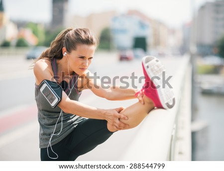 An athletic woman stretches out before going on a long run. She is wearing a cuff on her arm that is holding her device. On it, she is listening to some motivational music. - stock photo