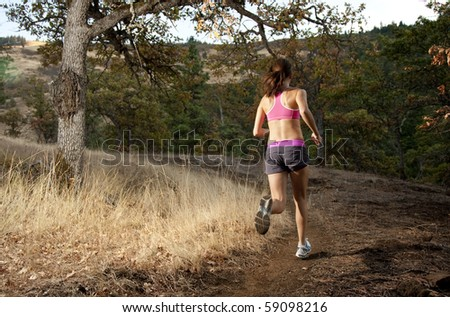 An athletic woman trail running in Oregon. - stock photo