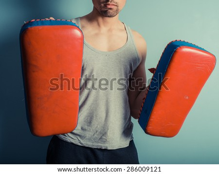 An athletic young man is holding pads and is ready for some muay thai or mixed martial arts training - stock photo