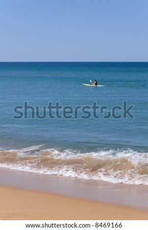 An athletic young man paddles a kayak on a beautiful blue day over a calm ocean. small wave lazily crashes onto shore. Plenty of copyspace - stock photo