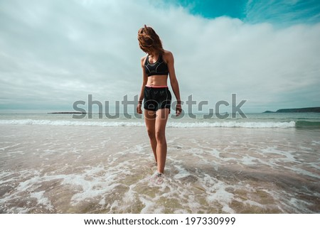 An athletic young woman is walking on the beach and is getting her feet wet in the surf