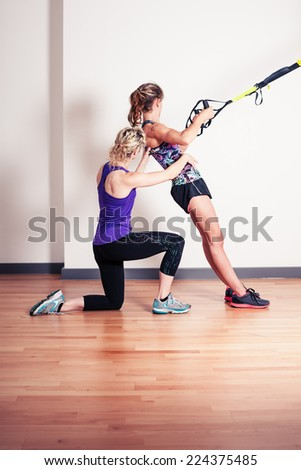 An athletic young woman is working out and is being corrected by her personal trainer - stock photo