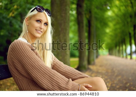 An attentive sexy young blonde woman in a tan jersey sits on a park bench looking upwards with empty tree lined avenue behind. - stock photo