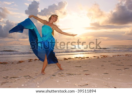 An attractive adult woman is dancing on the beach with the sun behind her , she appears to be happy and carefree. - stock photo