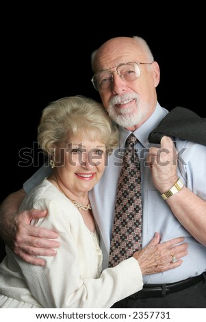 An attractive, affectionate senior couple on a black background. - stock photo