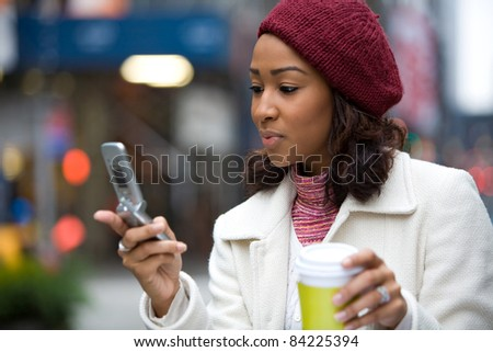 An attractive African American business woman checks her cell phone in the city.  She could be text messaging or even browsing the web via wi-fi or 4G connection. - stock photo