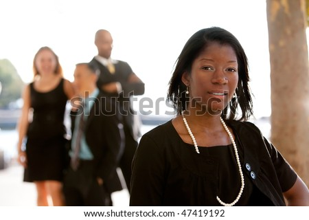 An attractive African American business woman with colleagues in the background