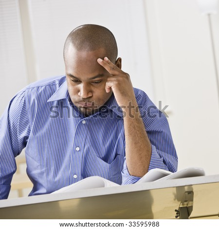 An attractive African-American male studying at a desk. He is resting his head against his fingers, and is puffing his cheeks out with air.  Square composition. - stock photo