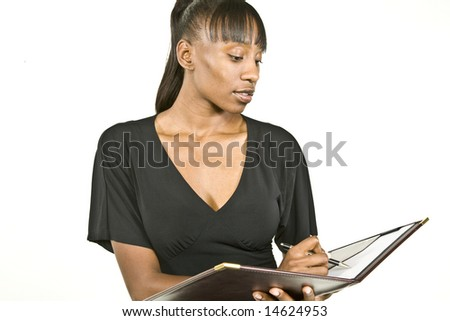 An attractive African American office worker, business woman or student taking notes.