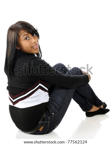 An attractive African American teen sitting on the floor, while looking back at the viewer.  Isolated on white. - stock photo
