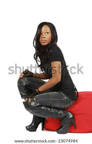 An attractive African American woman crouching on a beanbag chair. - stock photo