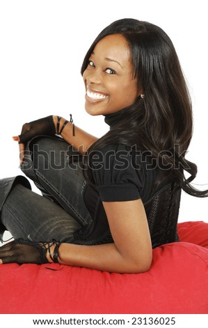 An attractive African American woman sitting on a beanbag chair. - stock photo