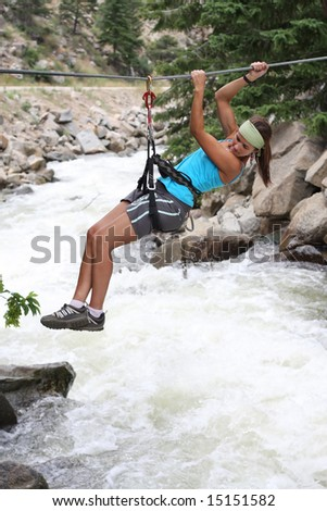 An attractive and atletic girl makes tyrolean traverse over a rushing river - stock photo