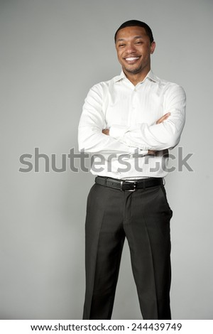 An attractive and happy African American boy wearing a white button down and black slacks on a gray background in a studio setting acting funny. - stock photo