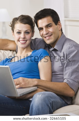An attractive and happy couple sitting together on a couch and using a laptop.  They are smiling directly at the camera.  Vertically framed shot. - stock photo