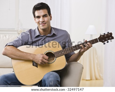 An attractive and relaxed looking man sitting on a couch and playing the guitar.  He is smiling at the camera. Horizontally framed shot.