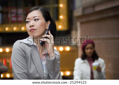 An attractive Asian business woman talking on her cell phone in the city. - stock photo