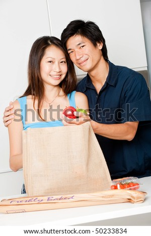 An attractive asian couple unpacking groceries in the kitchen at home - stock photo