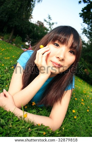 An attractive Asian woman laying on grass holding flower her head in hand - stock photo