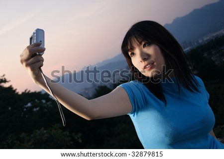 An attractive Asian woman taking a picture of herself with sunset mountains - stock photo
