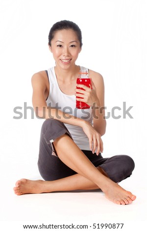 An attractive asian woman with sports drink on white background - stock photo