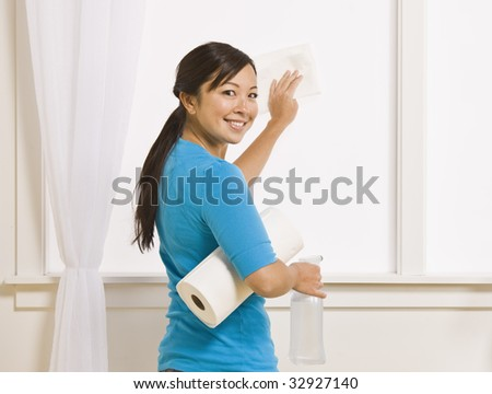 An attractive asian young female washing a window. She is holding a roll of paper towels and has her head turned to smile toward the camera. Horizontally framed photo. - stock photo