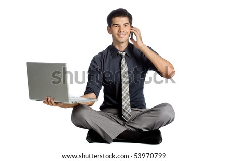 An attractive athletic businessman doing a yoga pose while using his mobile phone and laptop against white background - stock photo