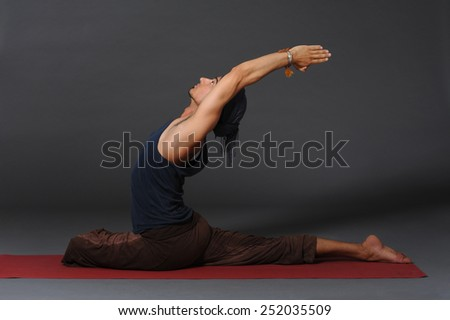 An attractive athletic man doing a yoga pose in studio on grey background. - stock photo