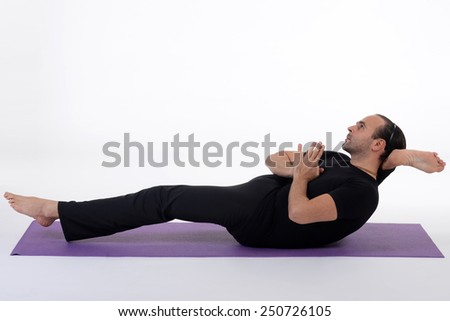 An attractive athletic man doing a yoga pose in studio on white background. - stock photo