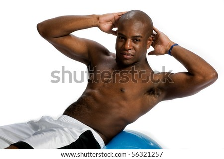 An attractive athletic man doing crunches on a fitness ball against white background