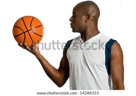 An attractive athletic man holding a basketball against white background - stock photo