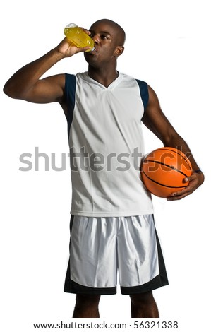 An attractive athletic man with a basketball drinking an energy drink against white background - stock photo