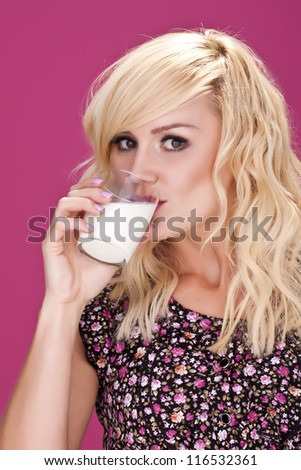 An attractive blond woman drinking a glass of milk. Milk is good for you. - stock photo