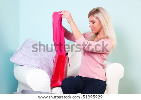An attractive blond woman sat at home looking at the new clothes she has just bought.
